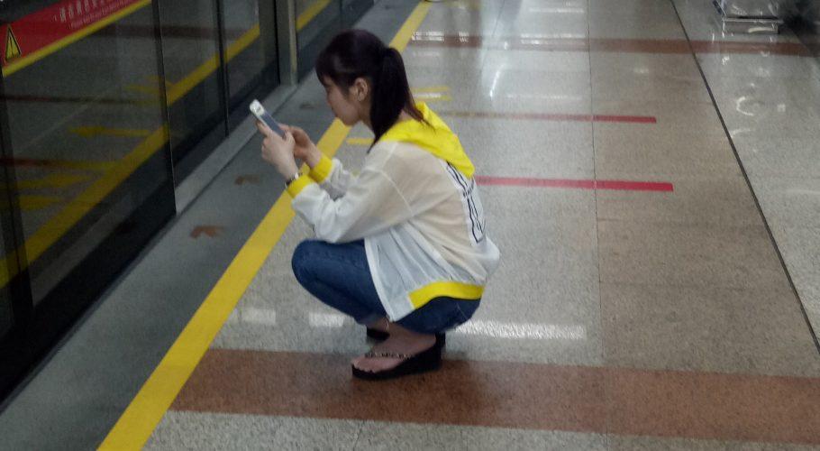 Chiense girl crouching at metro