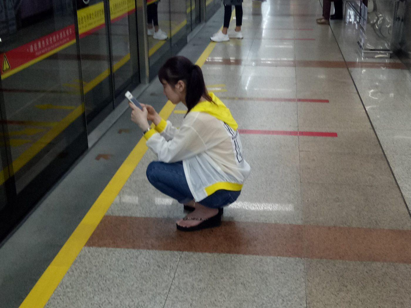 Chiense girl crouching at metro